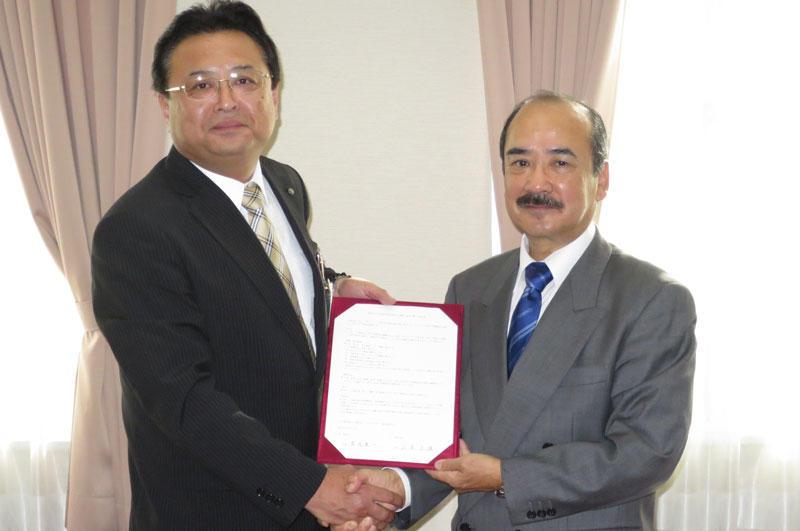 署名した協定書を手に握手する吉久光一学長(右)と山本正雄区長