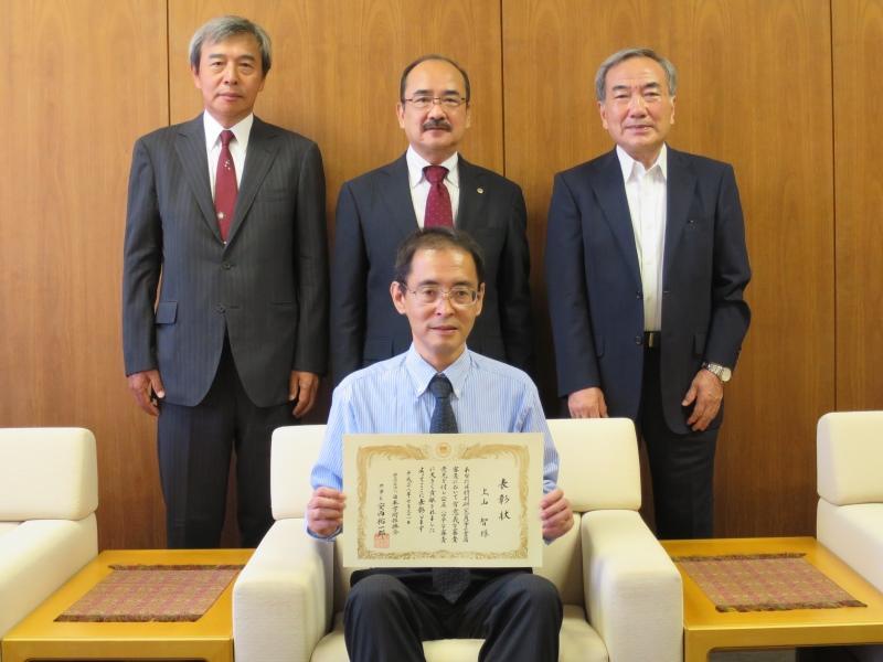 表彰状を手に記念写真に収まる上山教授(前列)