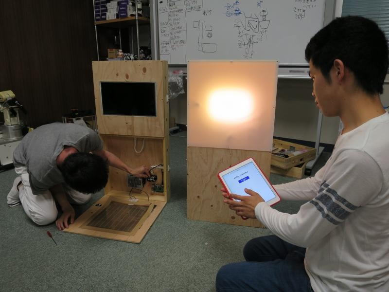 タブレット端末で照明をつける大江さん(右)=天白キャンパス2号館で