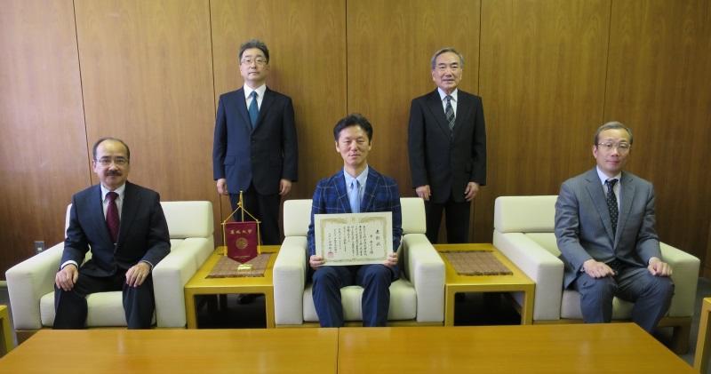 表彰状を手に記念写真に納まる李教授(前列中央)