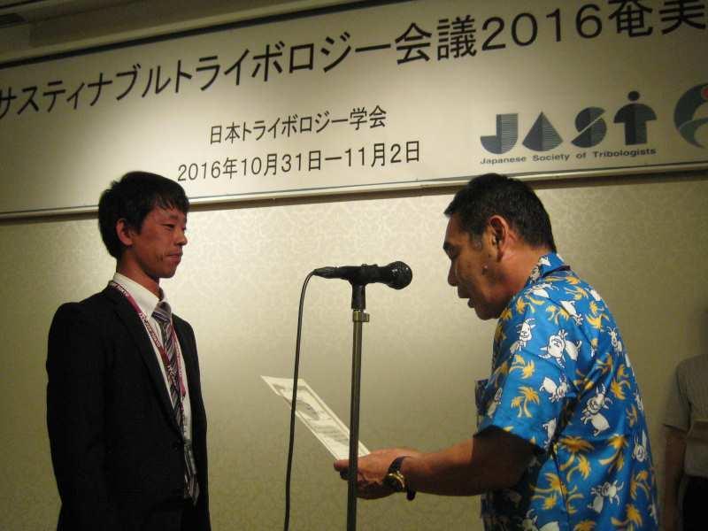 本会議の実行委員長である宇佐美初彦教授(本学理工学部)から表彰状を受けた小林さん(左)