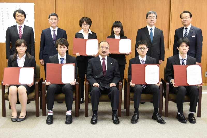記念写真に収まる奨学生らと吉久光一学長