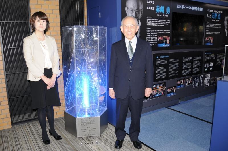 本学附属図書館の青色LEDモニュメント(生田京子准教授研究室の学生がデザイン)と赤﨑終身教授(右)、生田准教授(左)