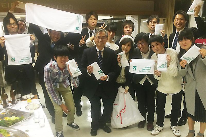 名古屋銀行の中村昌弘頭取(中央)と同企画の記念タオルを手に記念撮影する本学学生と中京大学の学生
