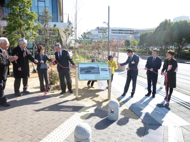 銘板を除幕した伊藤東区長(右から3人目)ら=ナゴヤドーム前キャンパスで