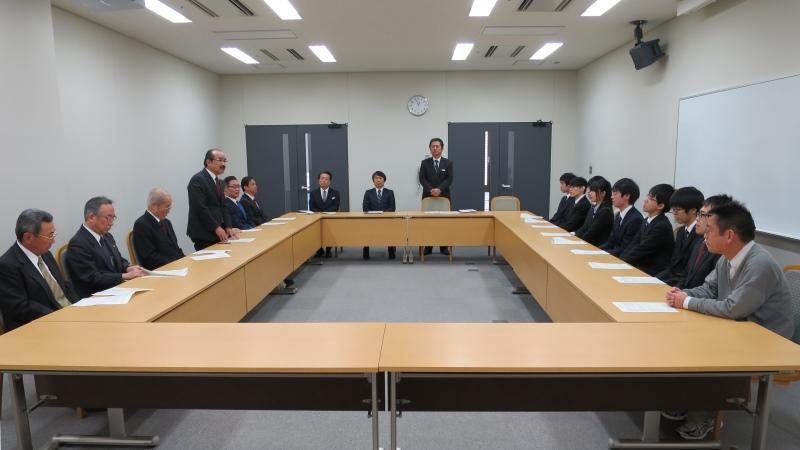 吉久光一学長(左側)から激励を受ける将棋部員(右側)=天白キャンパスのタワー75で