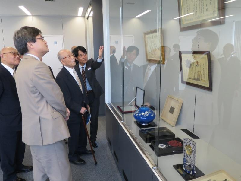 ガラスケースに展示された各種の表彰状を見る赤﨑終身教授と天野特別栄誉教授