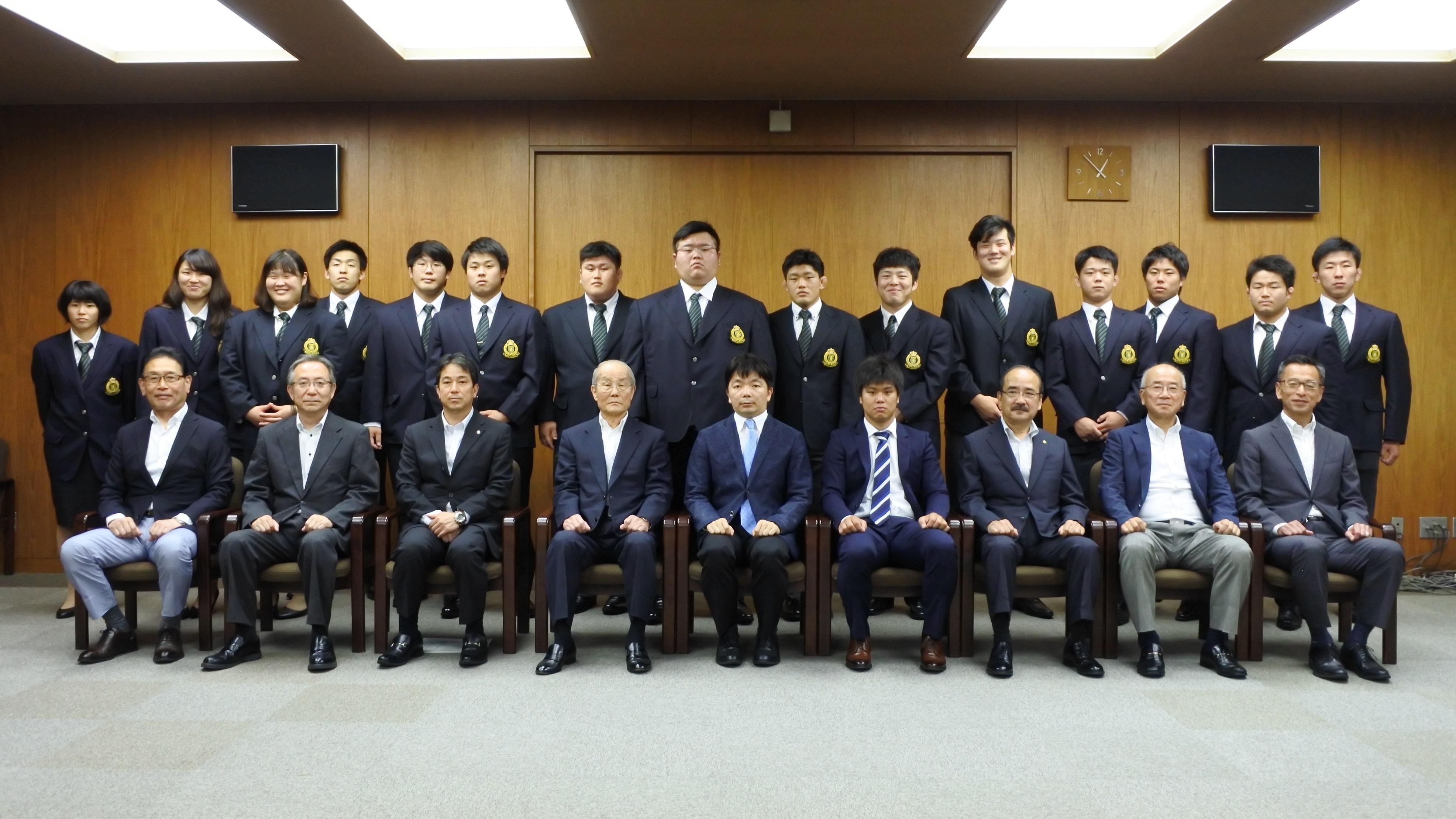小笠原日出男理事長、吉久光一学長らと記念写真に納まる柔道部員ら