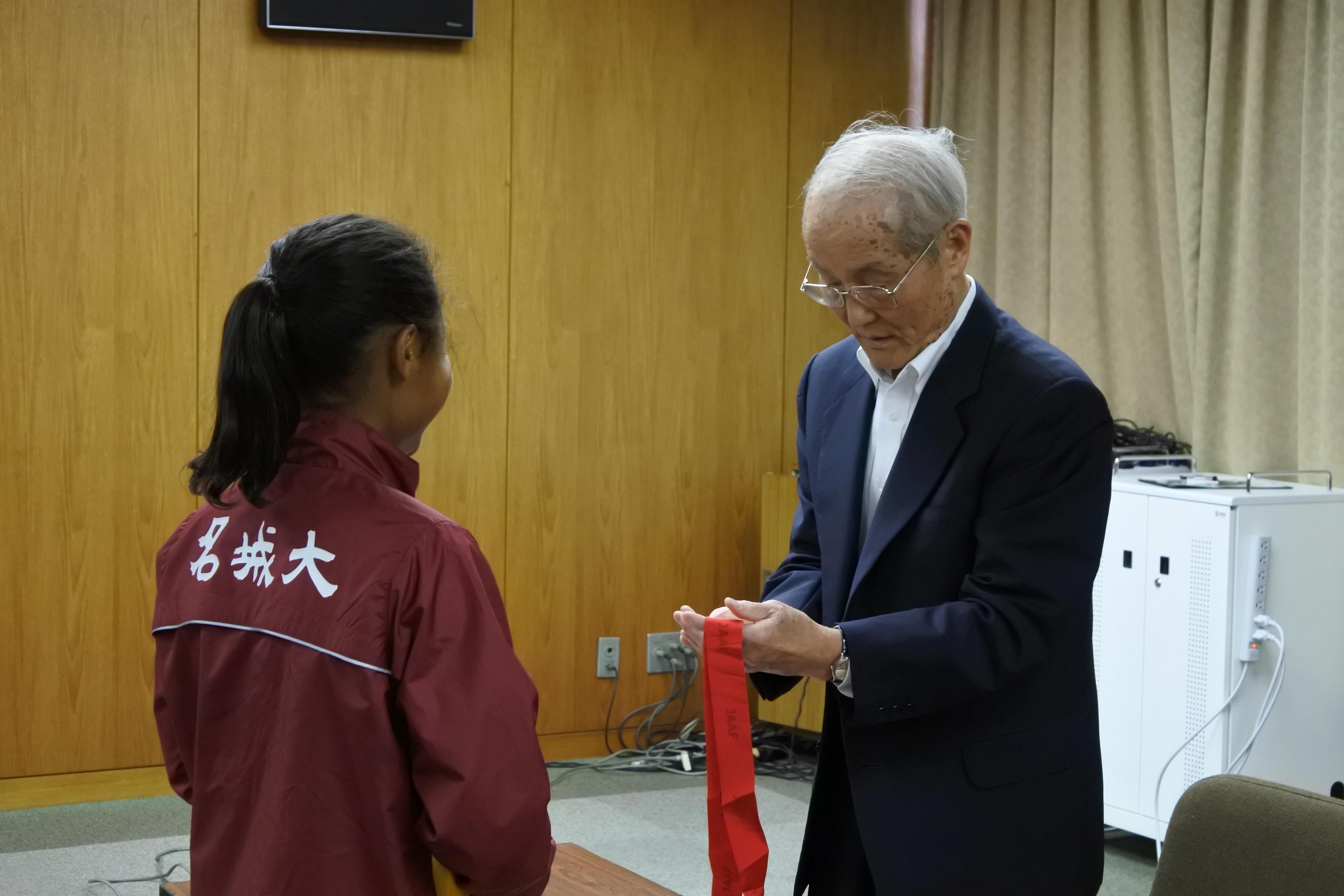 獲得したメダルを手に取る小笠原理事長