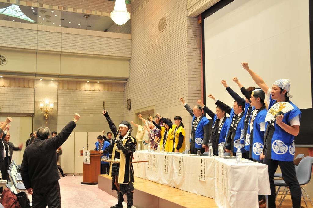 名古屋城前の集客施設が「金シャチ横丁」に決まり、名古屋おもてなし武将隊の音頭で勝ち鬨をあげる参加者たち