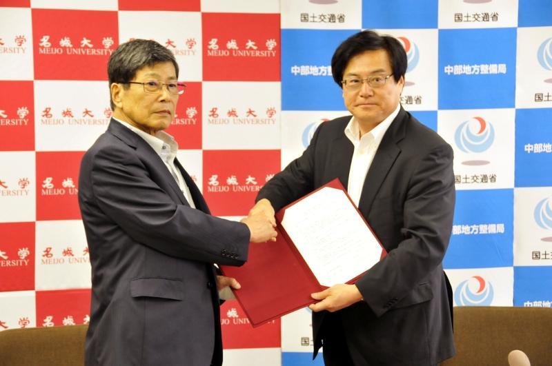 連携協定締結書に署名し握手を交わす中根学長と八鍬局長(右)
