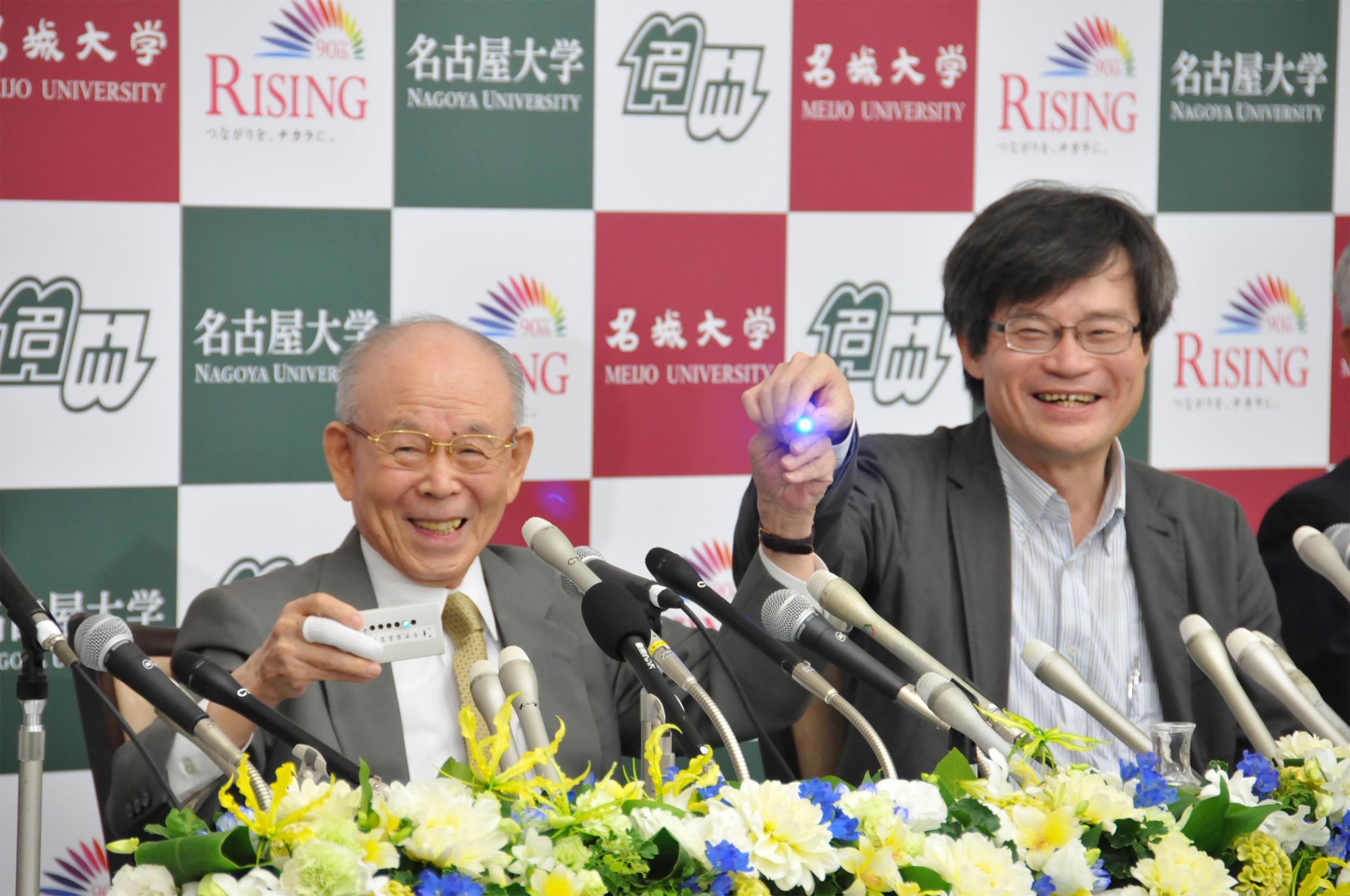 青色LEDを手に笑顔の赤﨑教授(左)と天野教授(10月10日、名古屋大学)