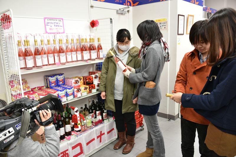 さっそくジェイビーズ売店で華名城ロゼワインを買い求める学生たち