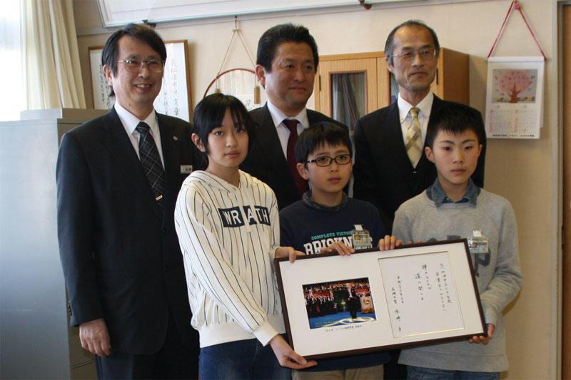 赤﨑終身教授に色紙を手にする児童代表の3人。後列は左から広瀬さん、青山課長、山崎校長