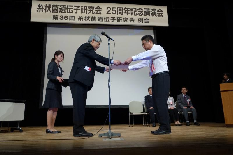糸状菌遺伝子研究会の塚越会長(名古屋大学名誉教授)から賞状を受け取る志水助教