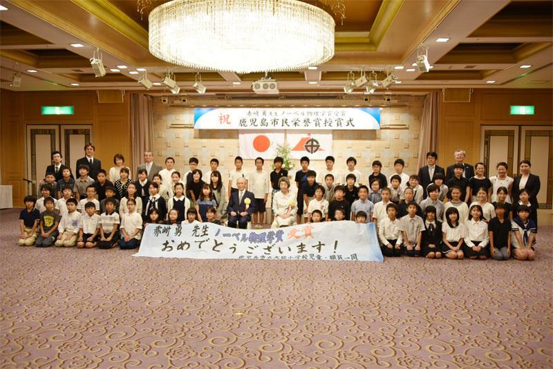母校の大龍小学校児童との交流会に出席し、記念撮影する赤﨑終身教授と陵子夫人(中央)