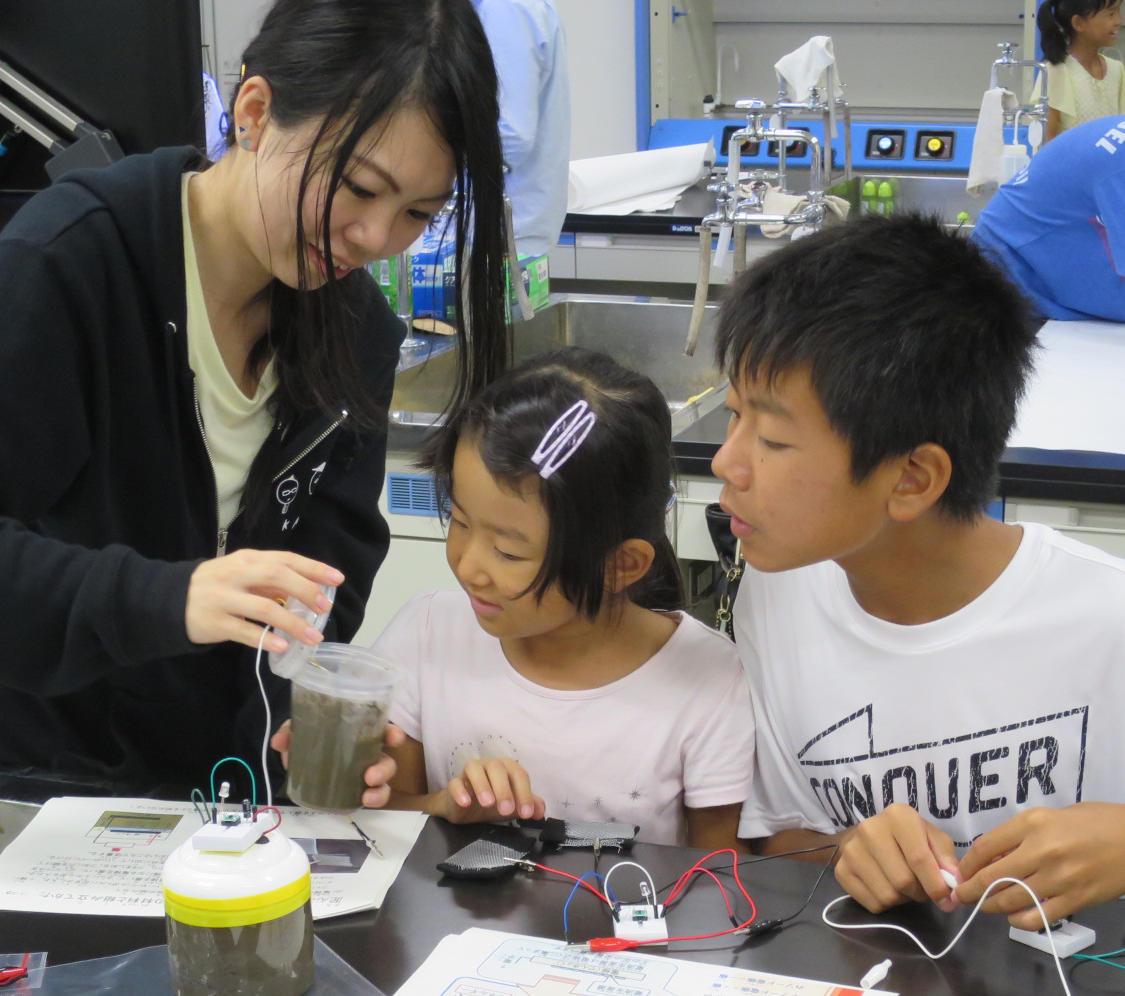土から電気を取り出す仕組みを学ぶ子どもたち