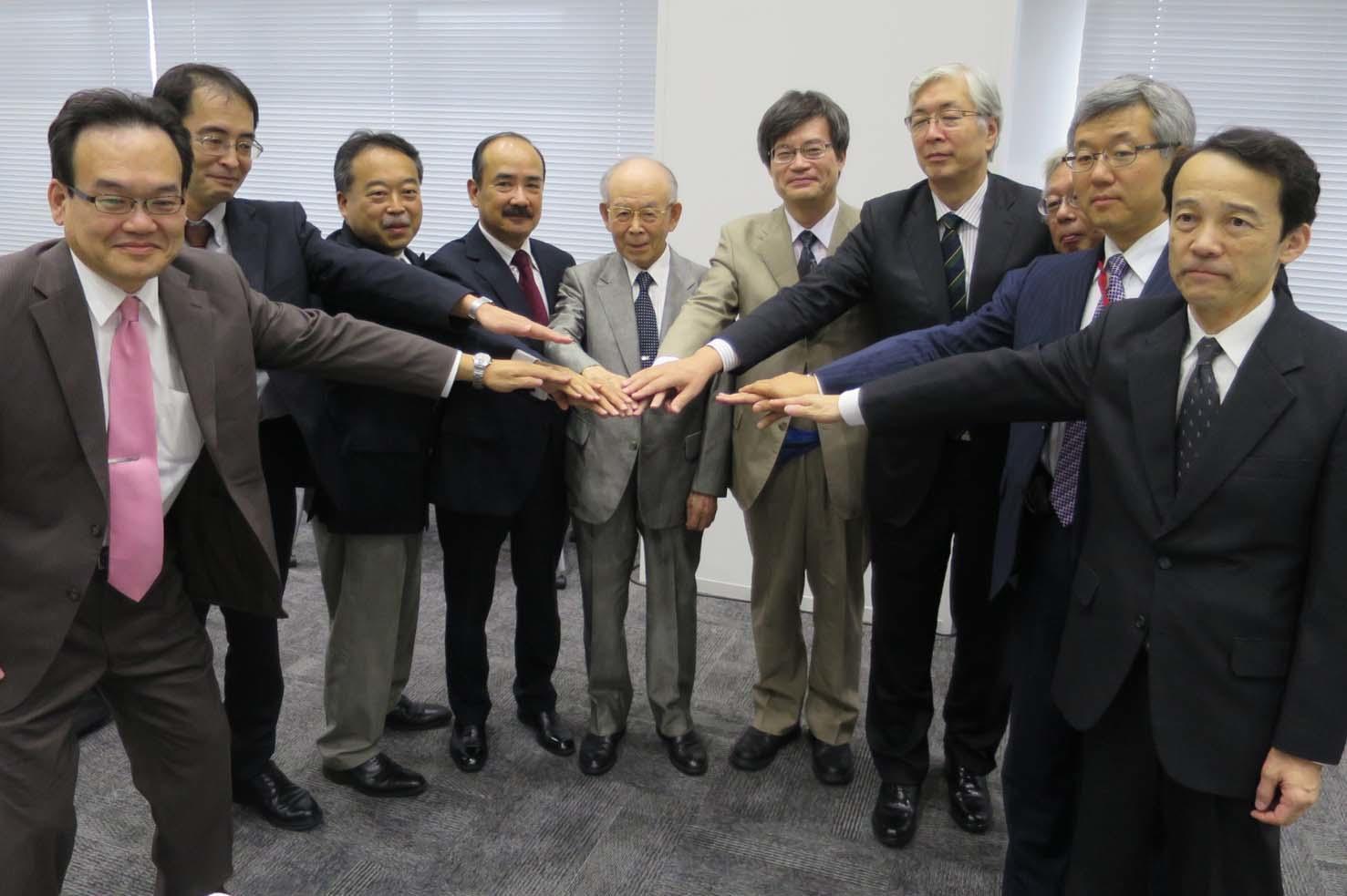 手を合わせ協力を誓う赤﨑終身教授、吉久学長、上山教授ら