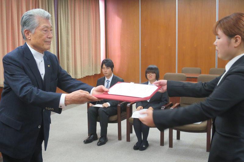 奨学生決定通知書を手渡す長谷川士郎氏(左)