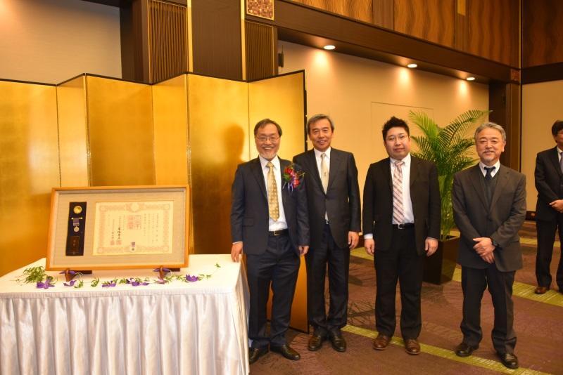 褒章・褒章の記と一緒に写真に納まる福田教授と加鳥理工学部長ら