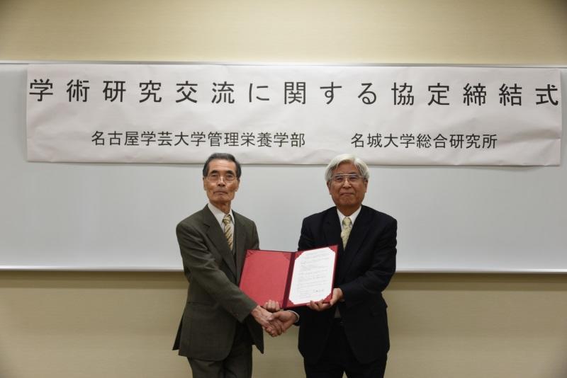握手をする名古屋学芸大学管理栄養学部の山中克己学部長(左)と伊藤総合研究所長