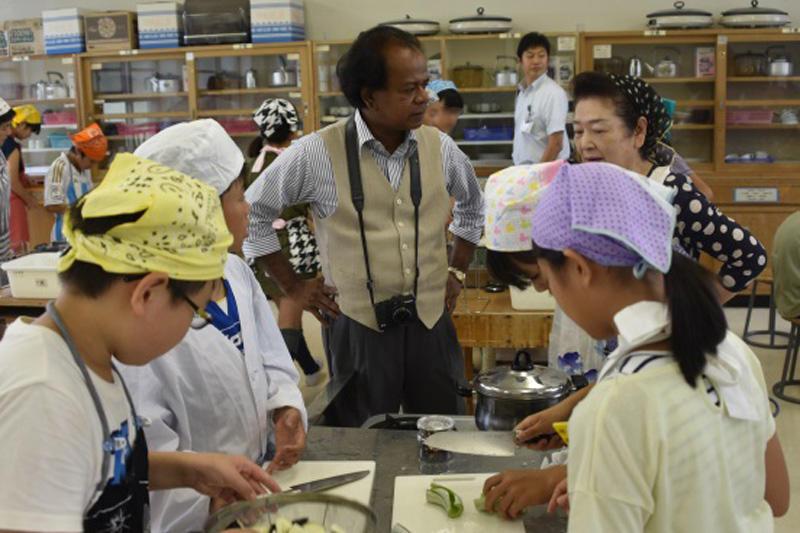 セイロン瓜が入った夏野菜カレーを作る児童たちと地域住民
