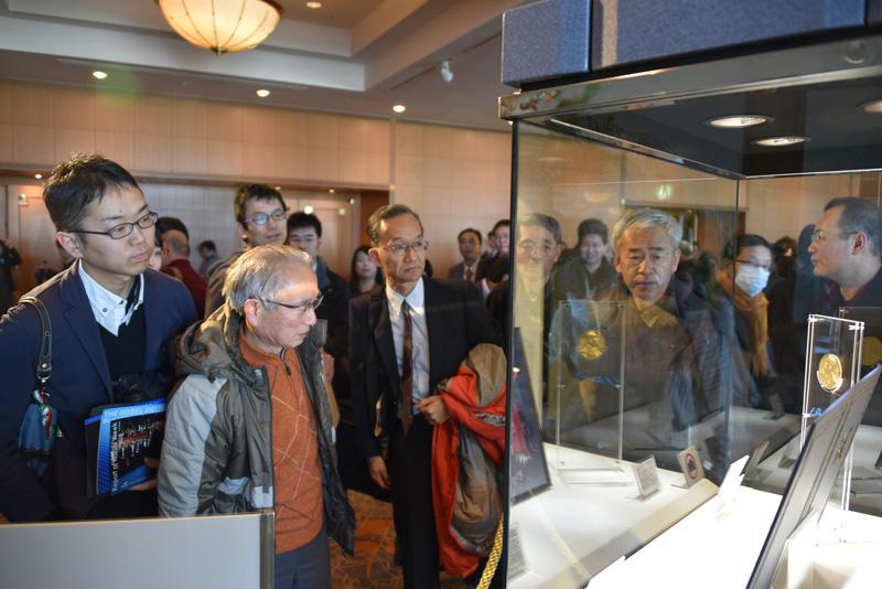 ノーベル物理学賞のメダルのレプリカに見入る人たち