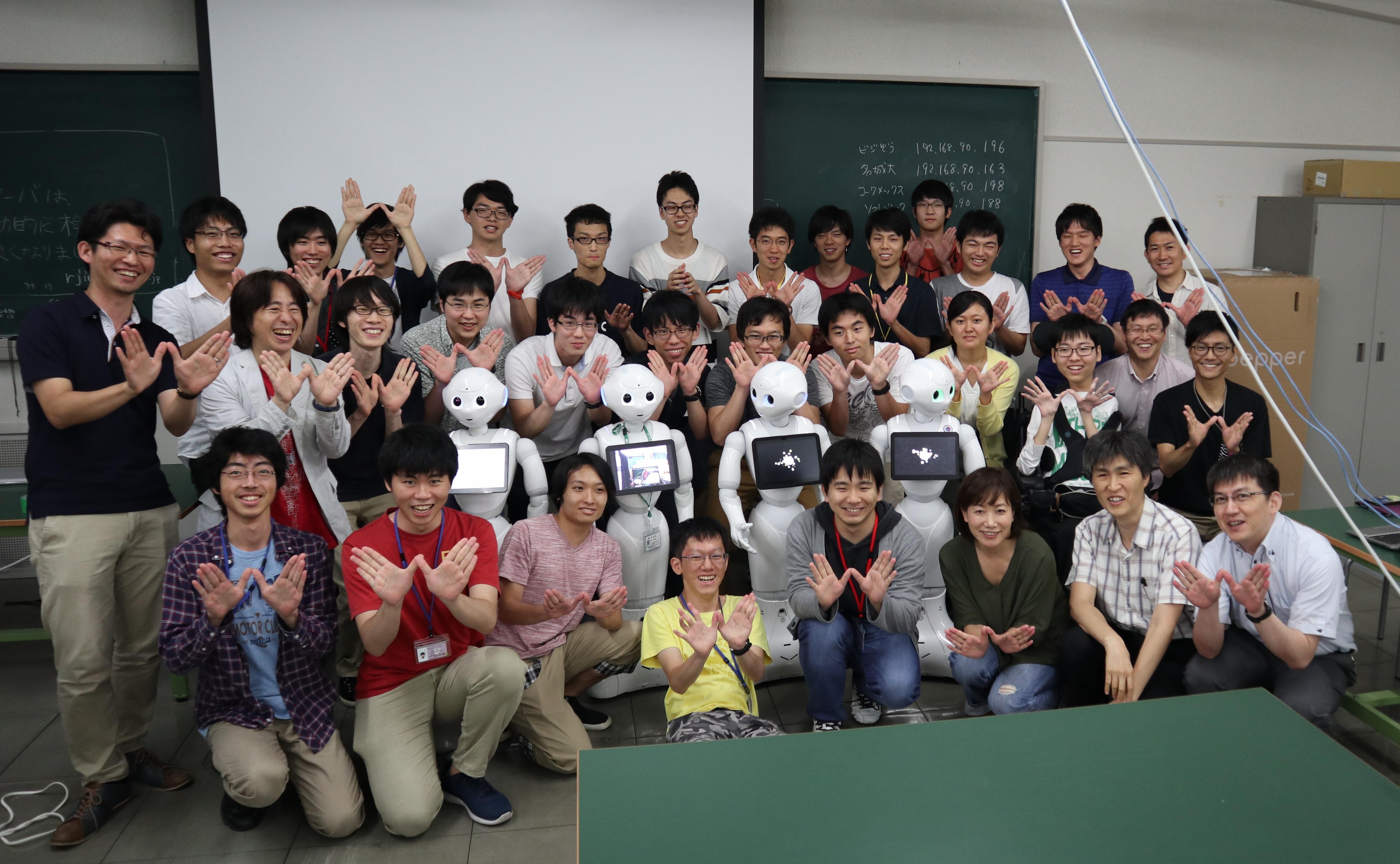 講師やサポートメンバーと記念写真に納まる学生ら