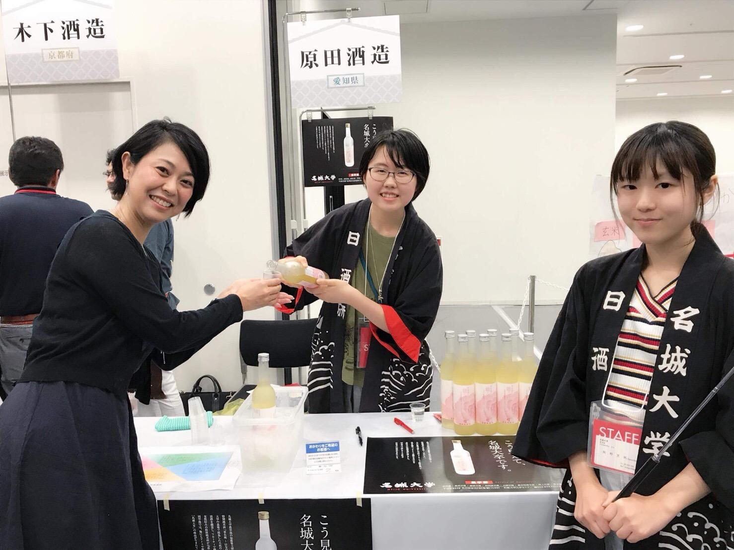 来場者へ「華名城」の試飲を勧める日本酒研究会メンバー