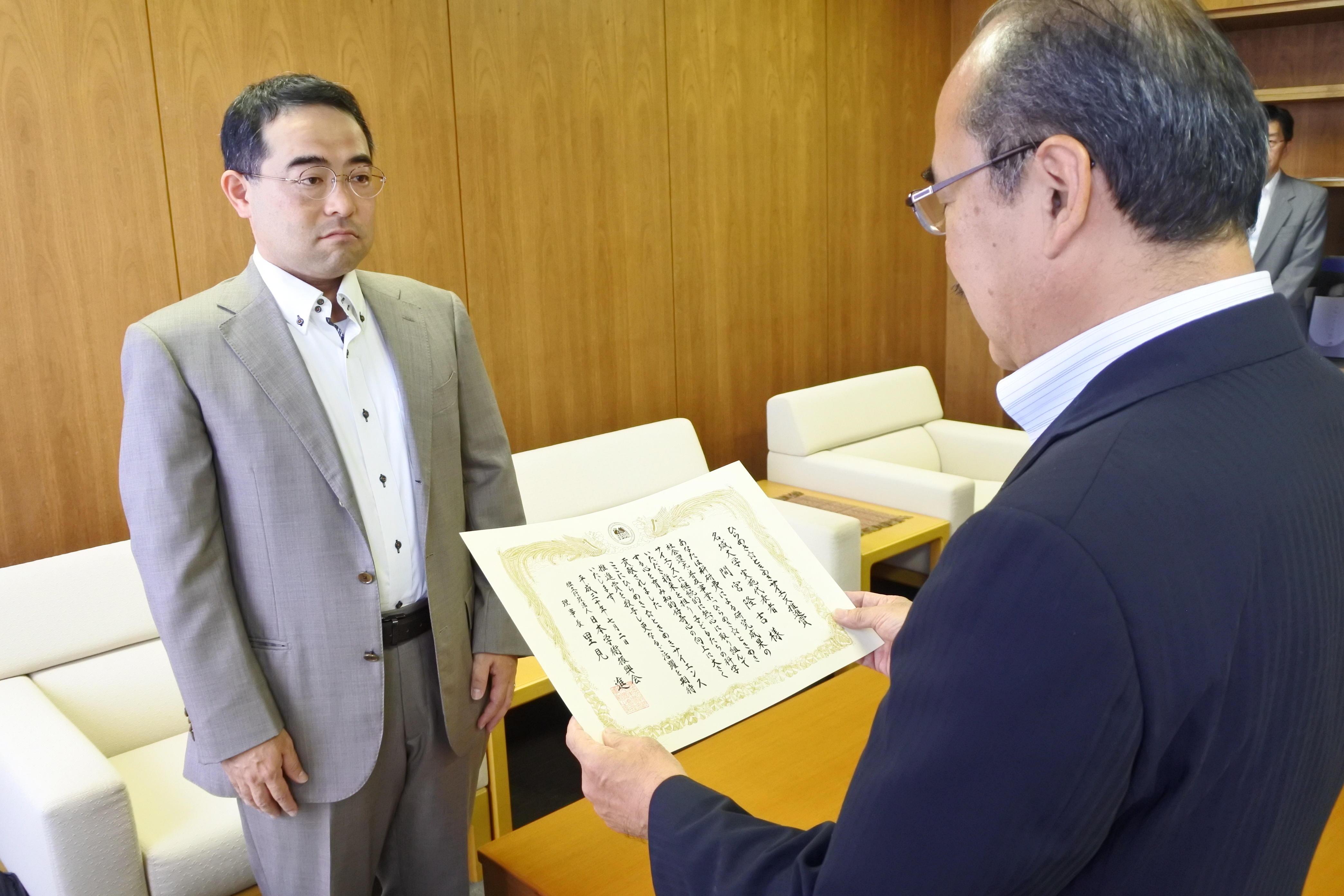 吉久学長(右)から表彰状を受け取る間宮准教授