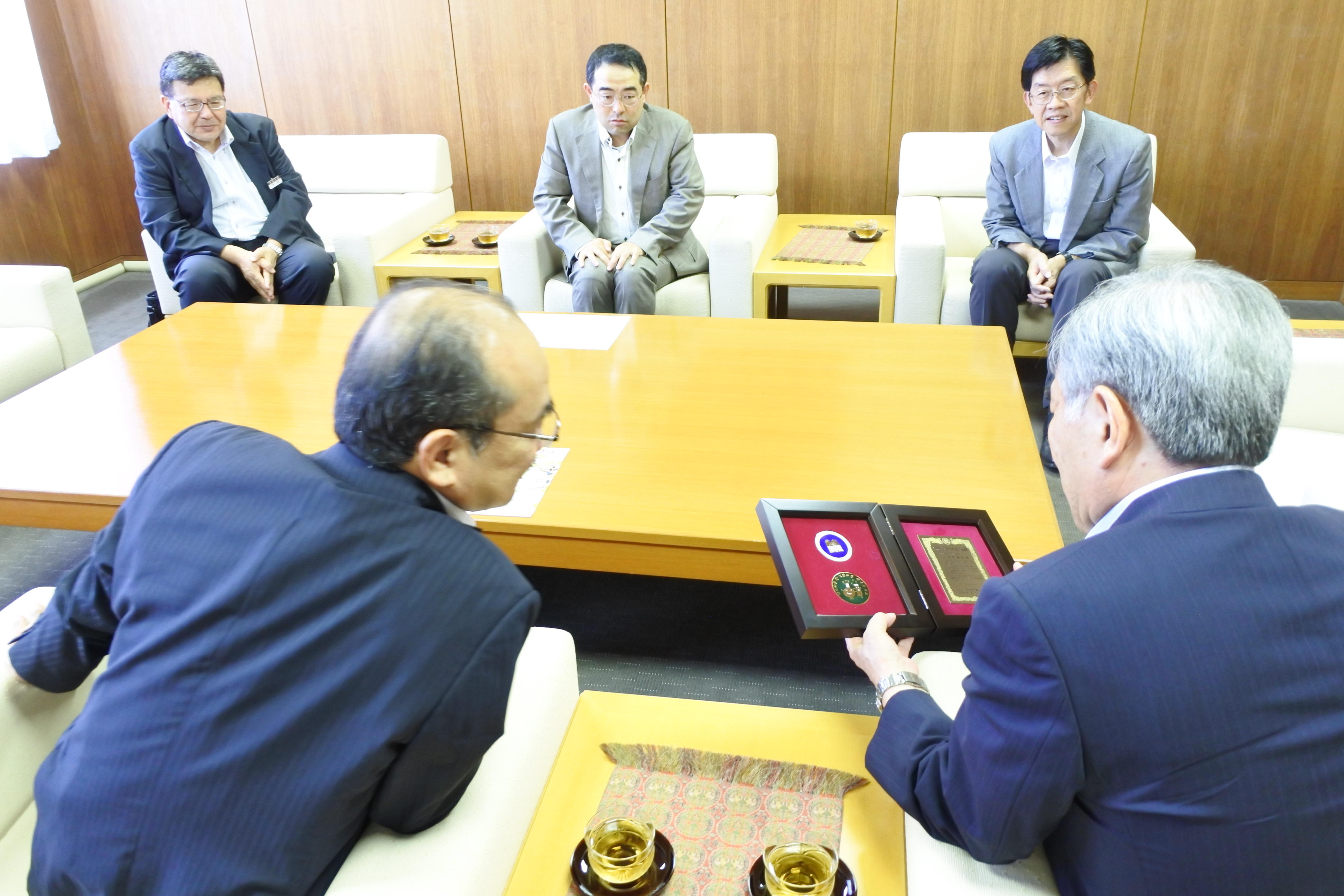 記念品の盾に見入る吉久学長(手前左)と原田健一学術研究支援センター長(同右)