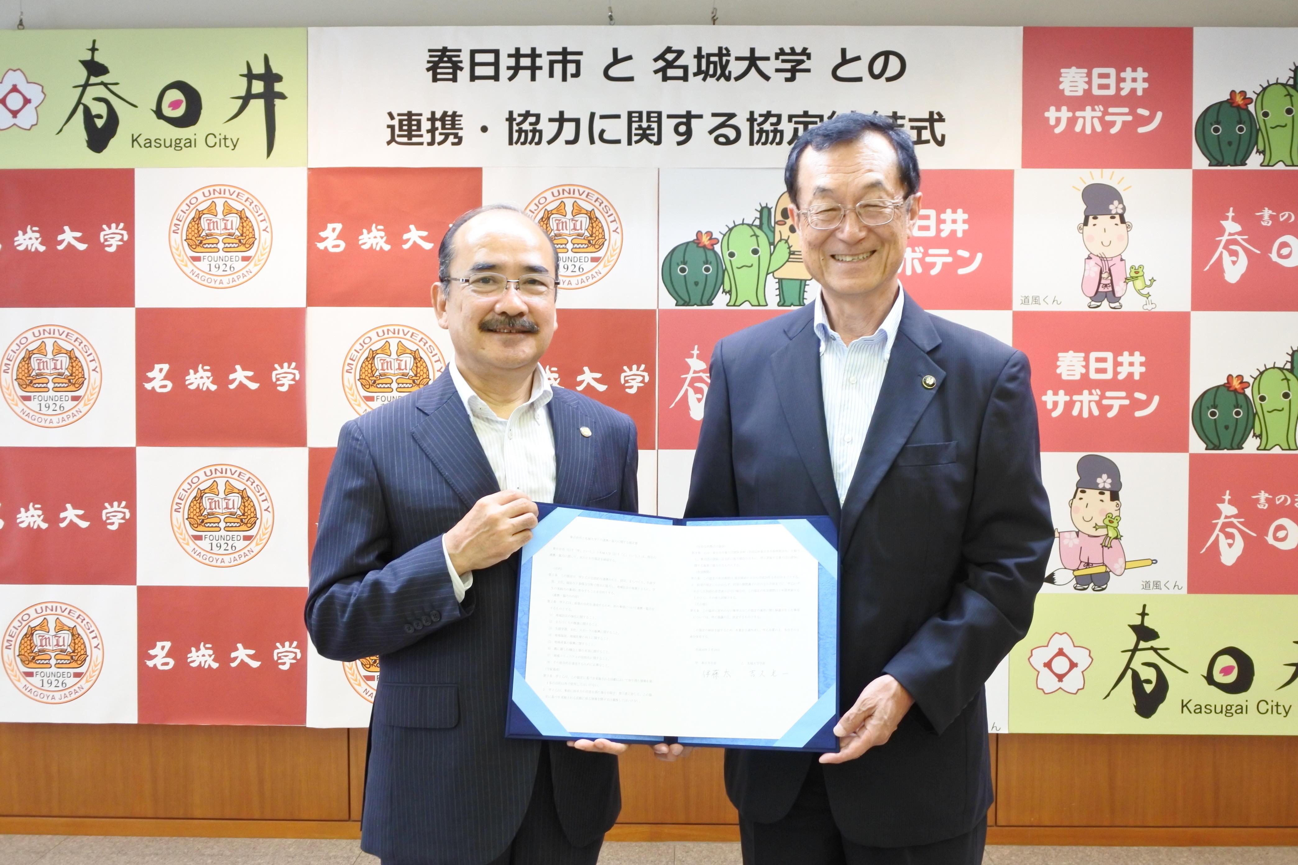 協定書を手にする吉久光一学長(左)と伊藤太市長