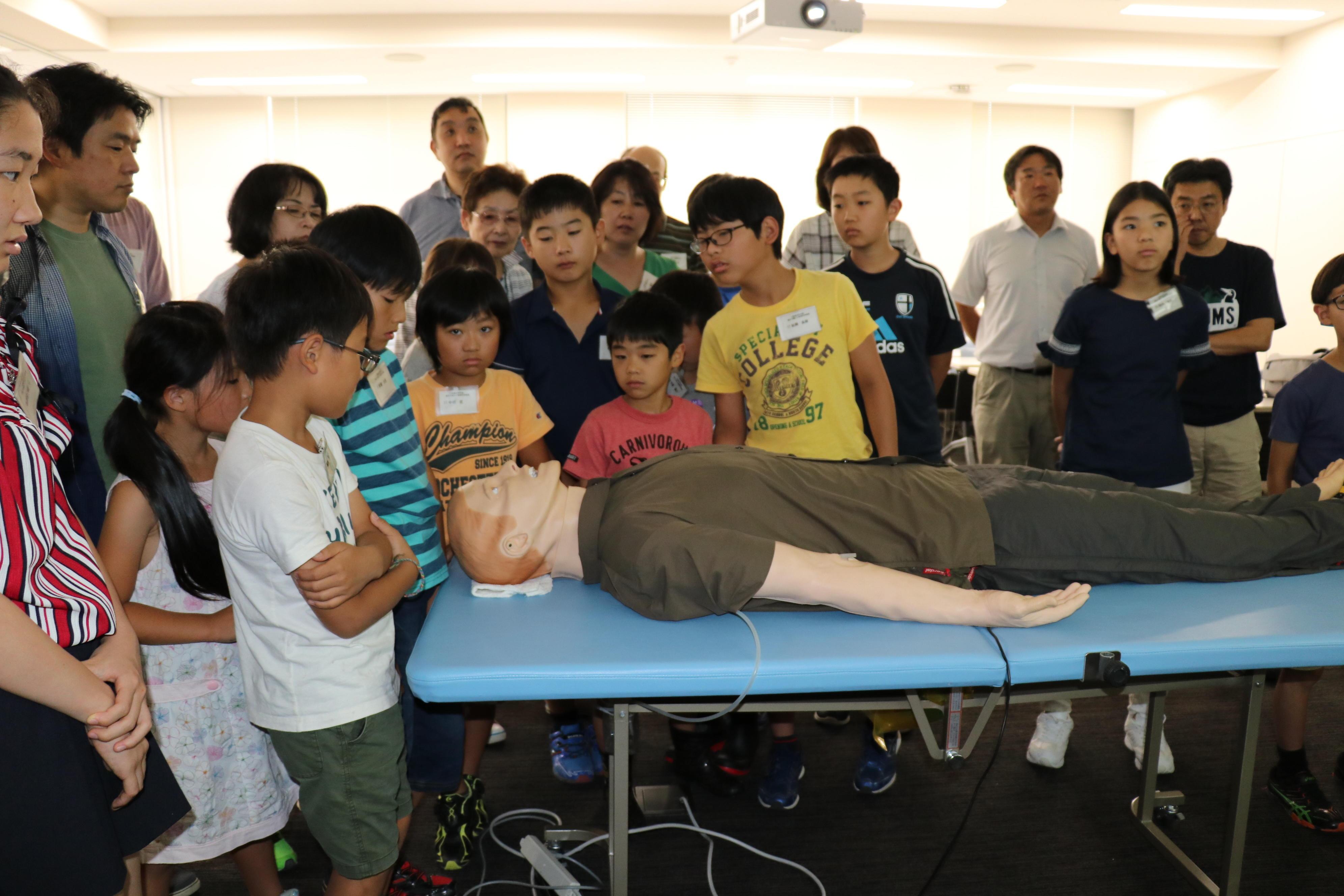 高性能患者シミュレーターを取り囲む参加者=八事キャンパス
