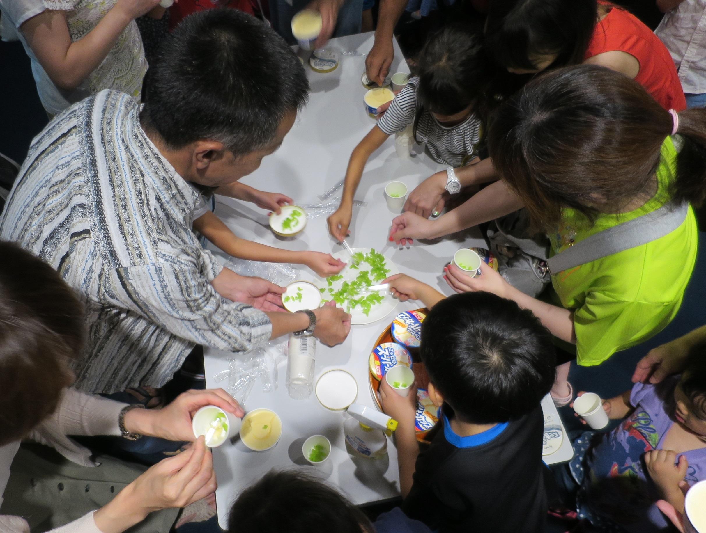 細かく切られたセイロン瓜の実に手を伸ばす親子ら