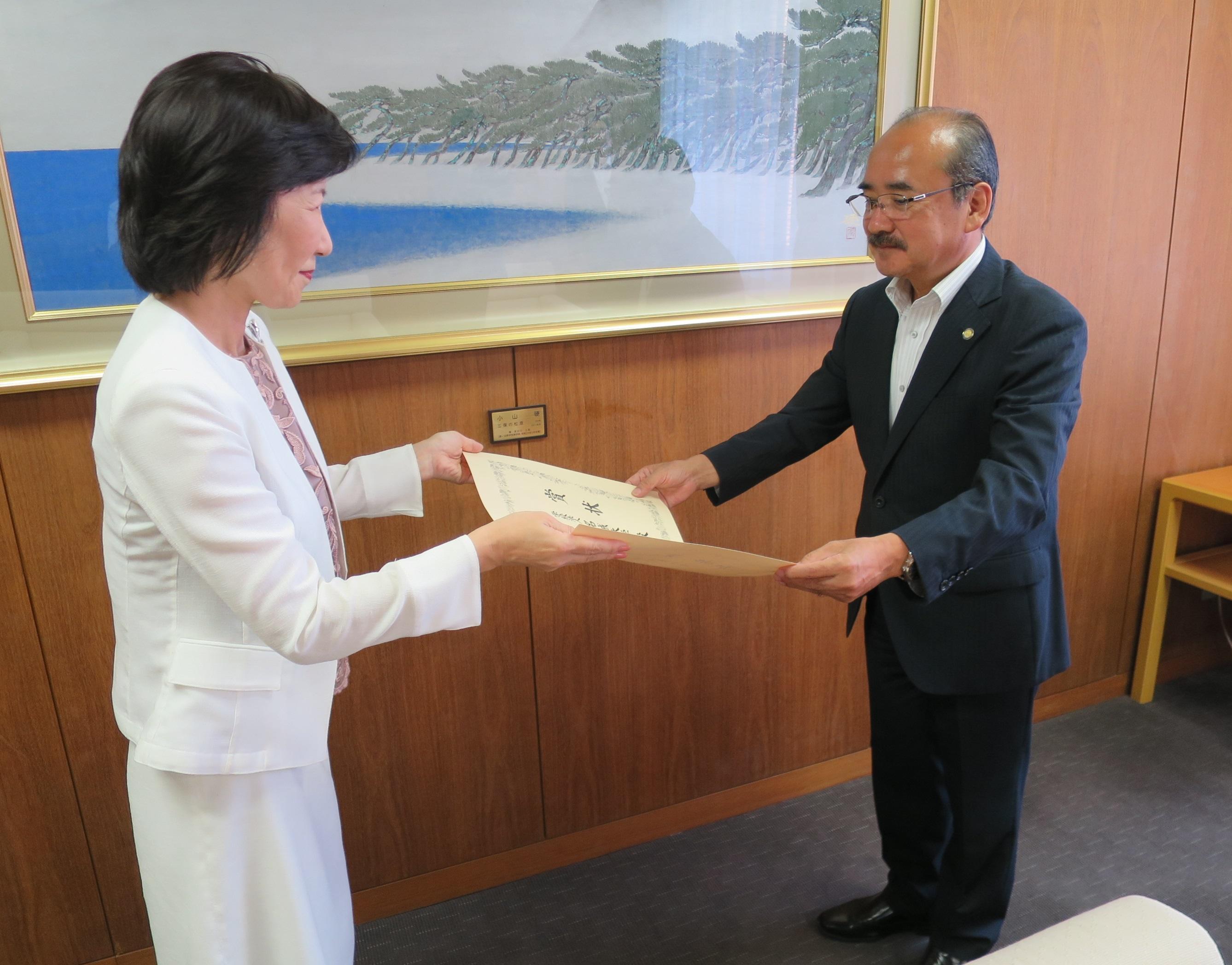 明石伸子理事長(左)から文部科学大臣賞の賞状を受け取る吉久光一学長