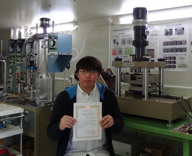 愛用する試験機の前で学会より贈られた表彰状を手にする高田さん