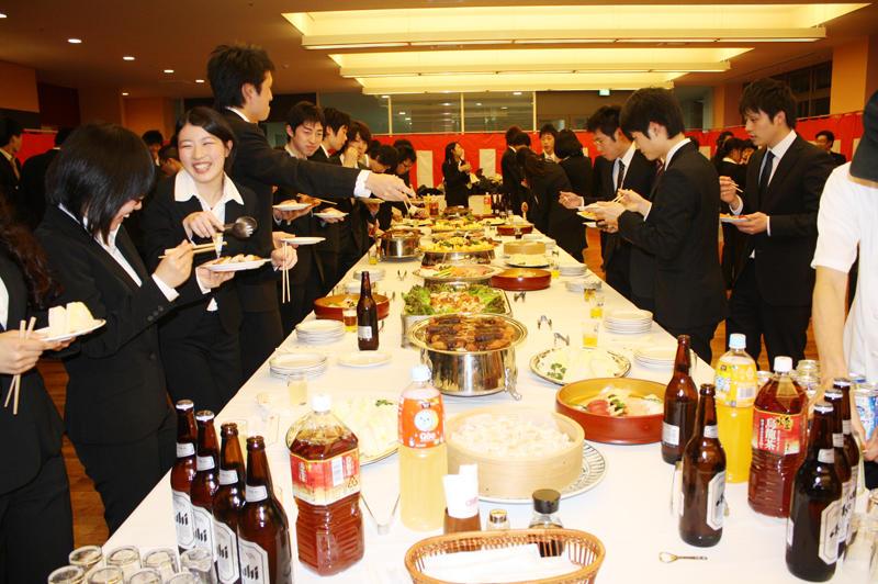 祝賀パーティーでさっそく料理にはしを伸ばす受賞者たち