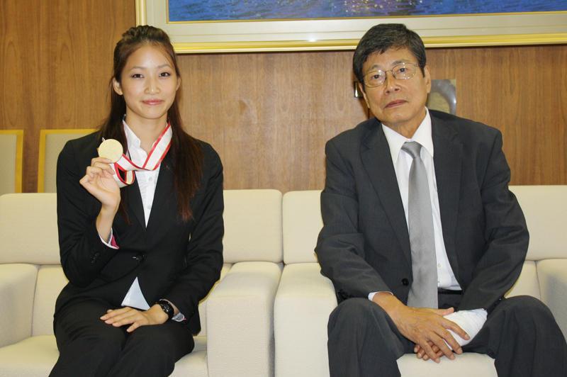 【写真】中根学長を訪れ、世界大会での金、アジア大会での銀メダルを報告する若松さん(10月1日、本部棟5階応接室で)