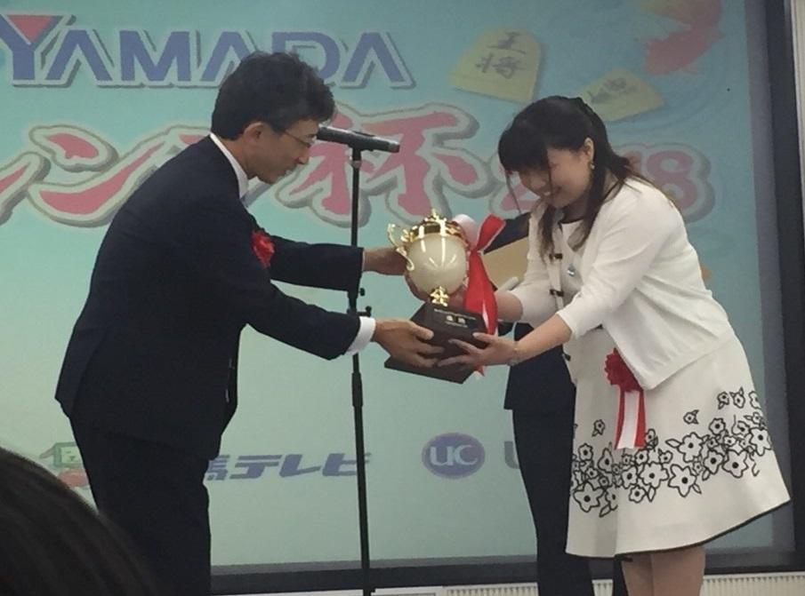 日本将棋連盟の佐藤康光会長(左)から優勝トロフィーを受ける中澤さん