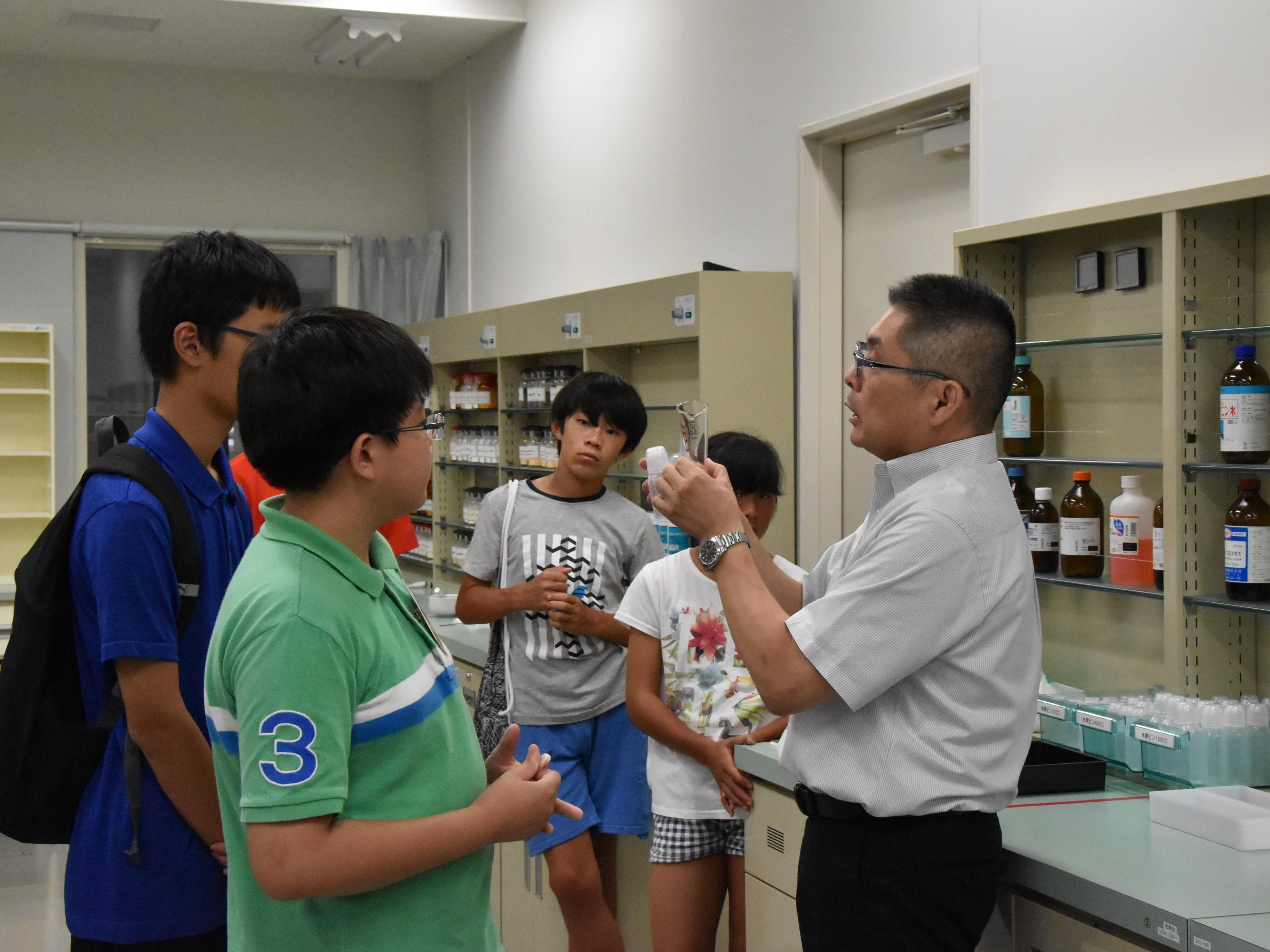 模擬薬局の説明をする黒野俊介薬学部教授(写真右)