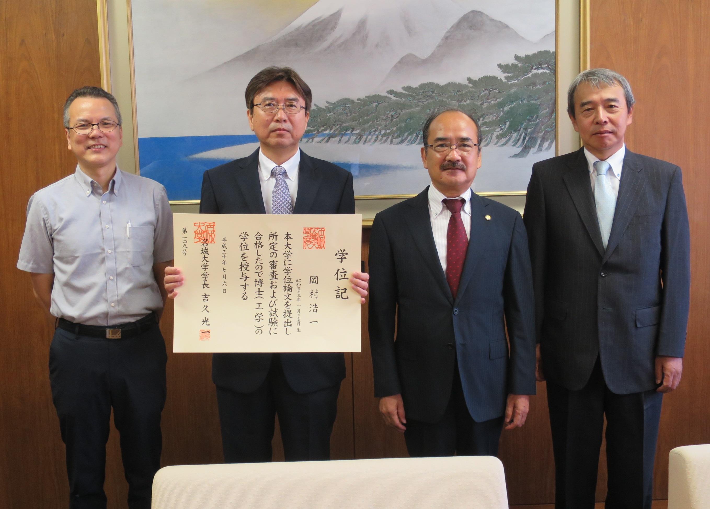 博士(工学)の学位記を手にする岡村浩一さんと吉久光一学長(右から2人目)ら