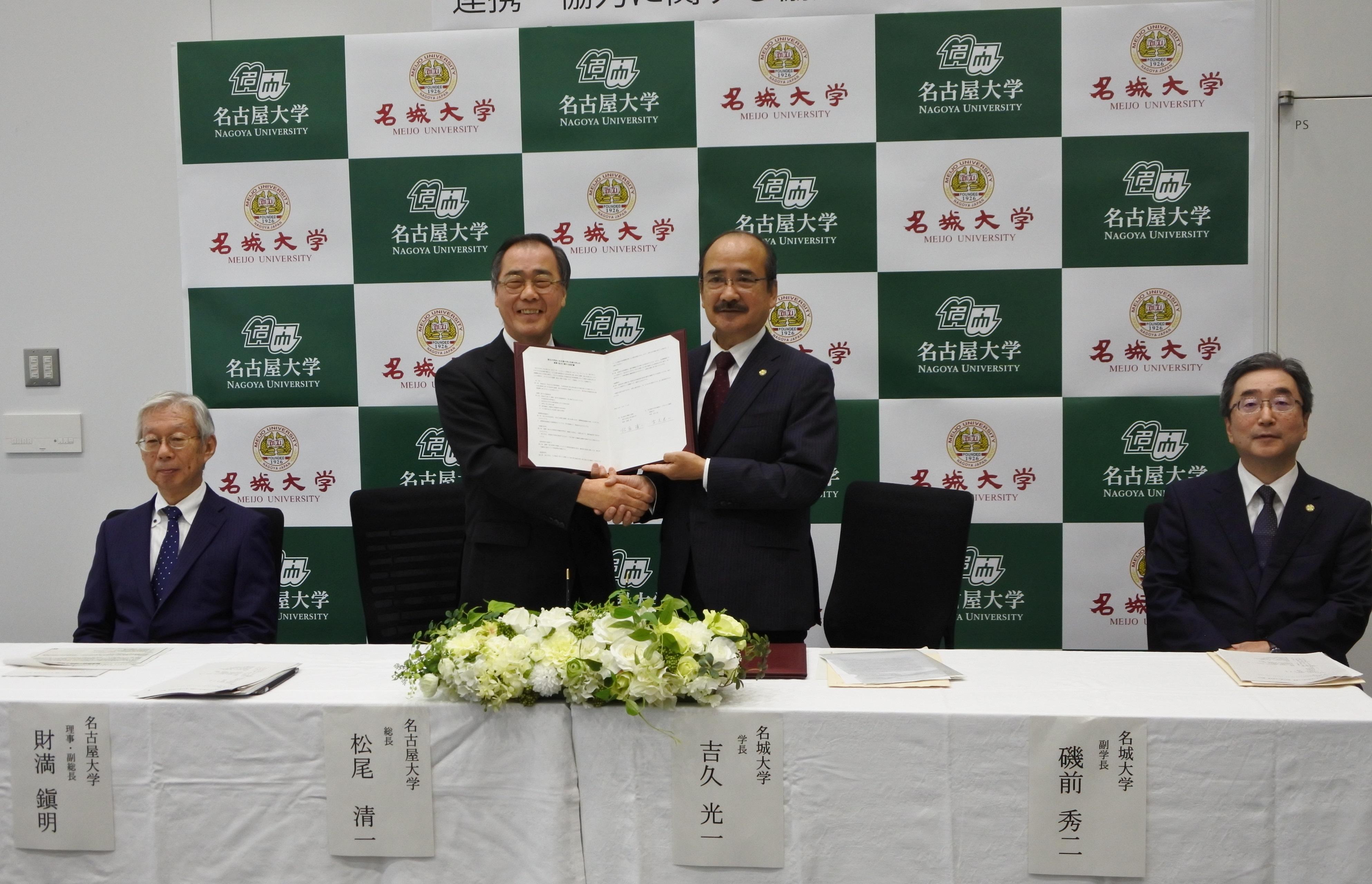 協定書を手に握手を交わす吉久光一学長(右から2人目)と松尾清一総長
