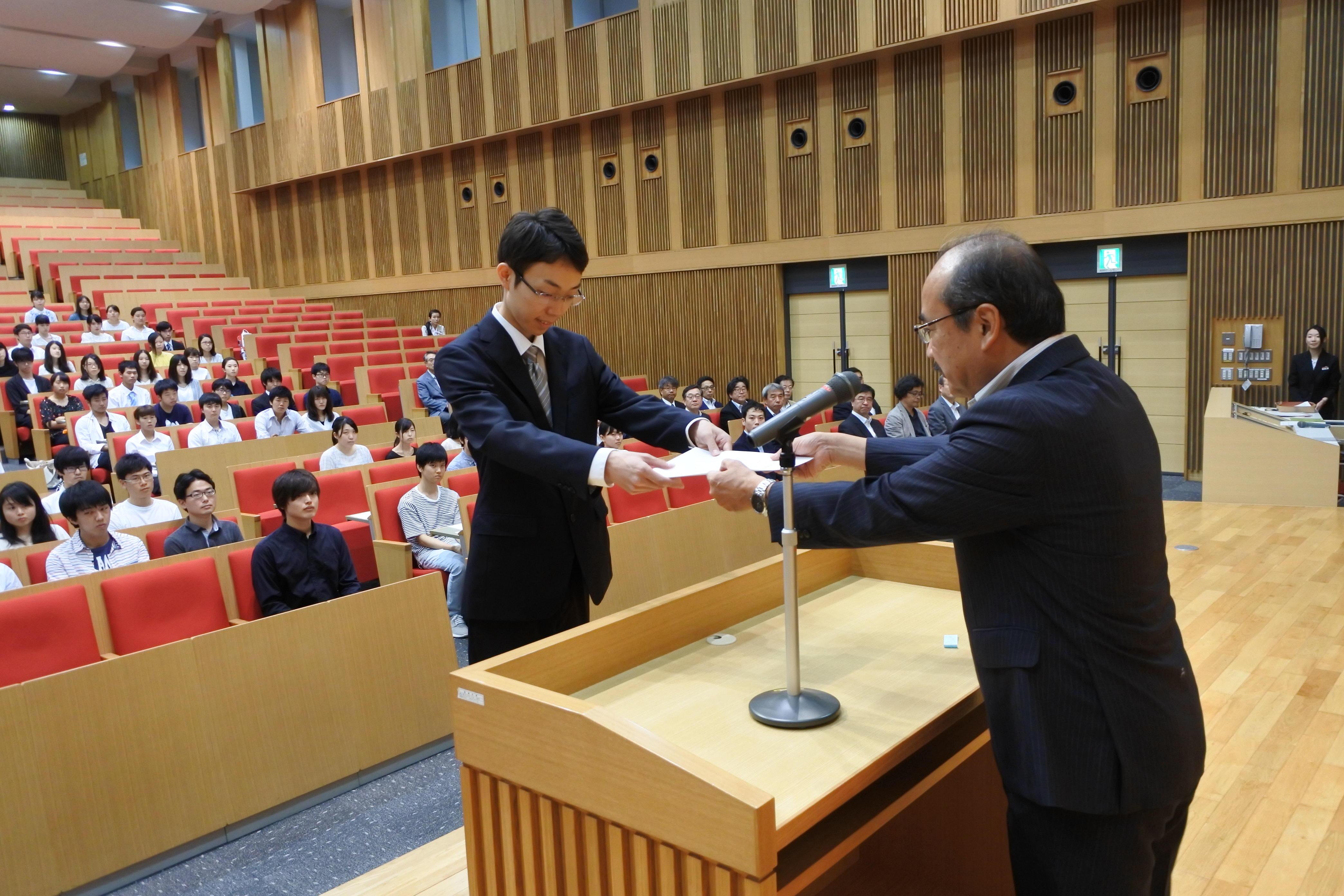吉久光一学長(右)から学業優秀奨学生決定通知書を受ける保木翔太さん