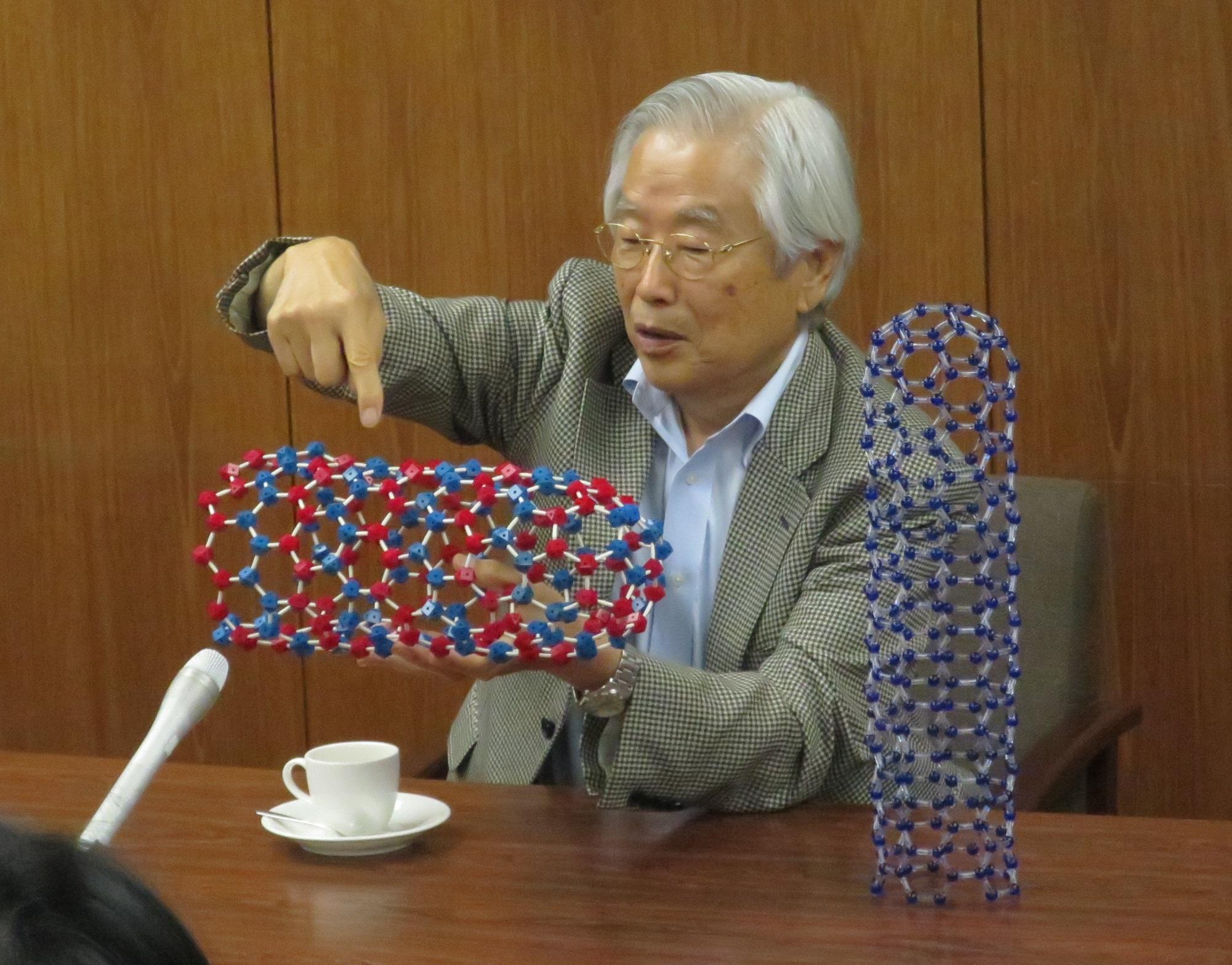 カーボンナノチューブの模型を手に説明する飯島終身教授