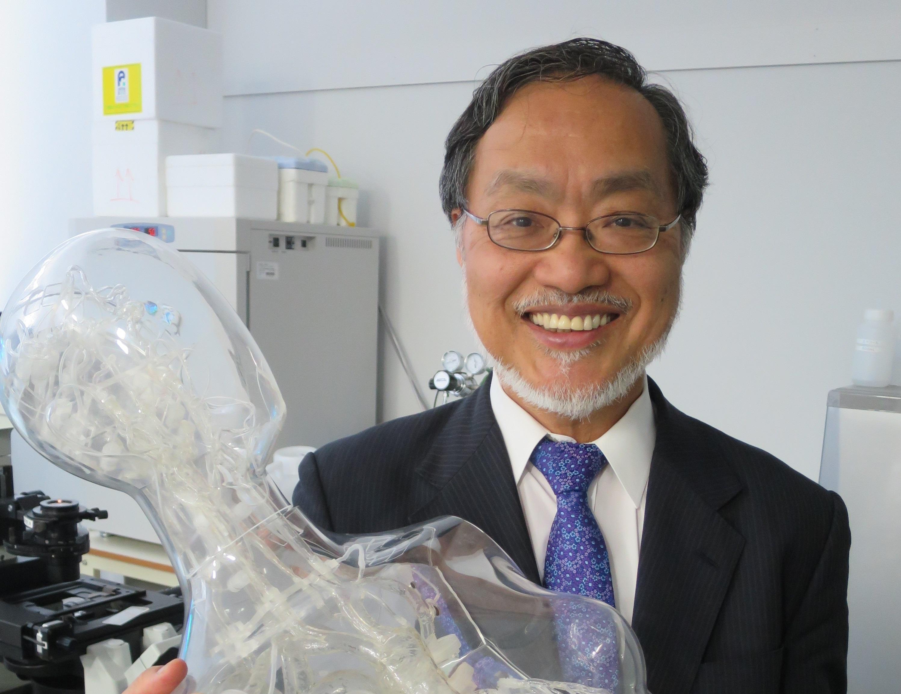人体の血管内治療技術トレーニング用シミュレーターを手にする福田教授