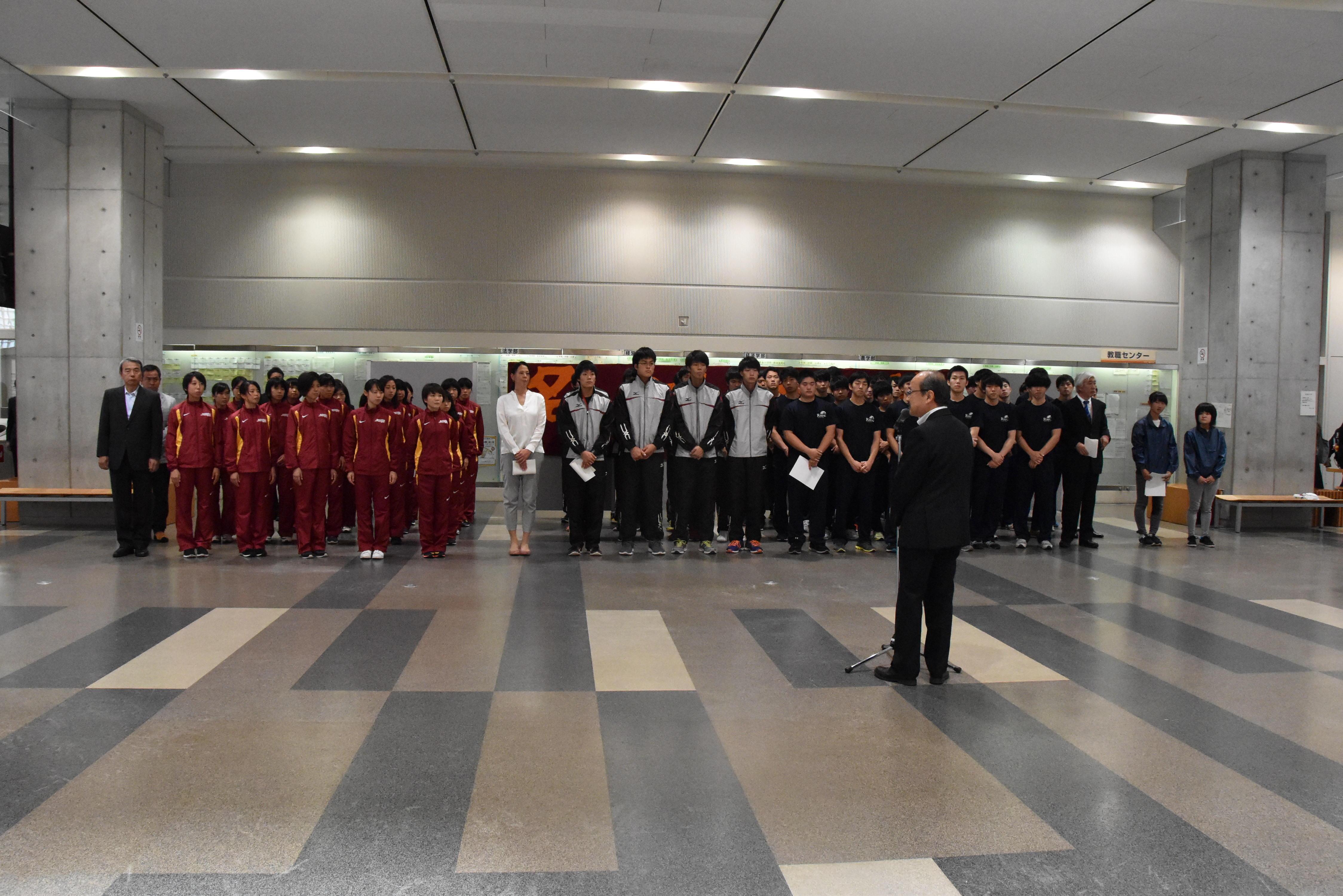 吉久光一学長(中央)の激励を受ける選手たち