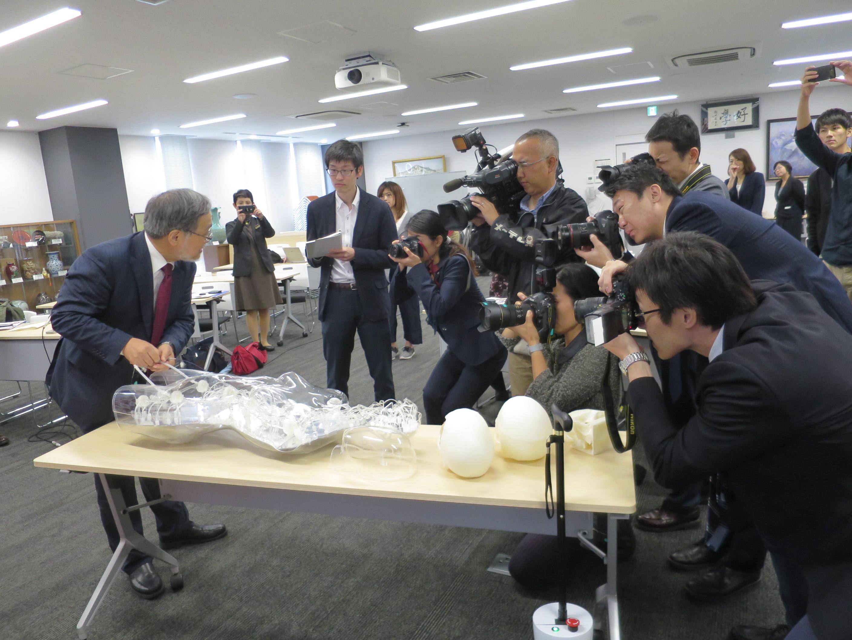 開発した人体の血管内治療技術トレーニング用シミュレーターをカメラの放列の前で操作して見せる福田教授