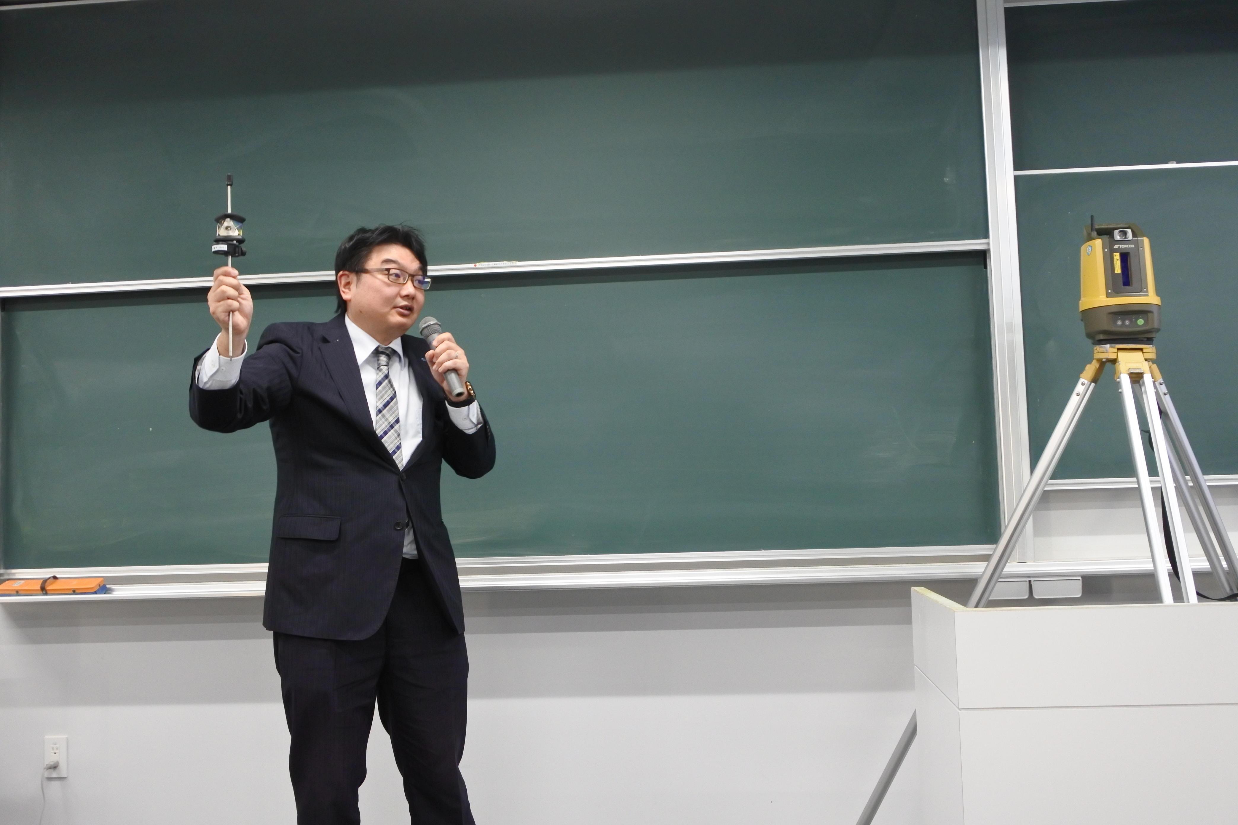 自動追尾トータルステーションを用いたデモンストレーションを行う柳田さん