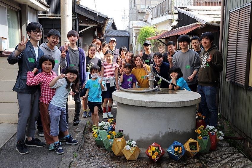 子どもたちと設置した植木鉢を囲んで写真に納まる学生ら