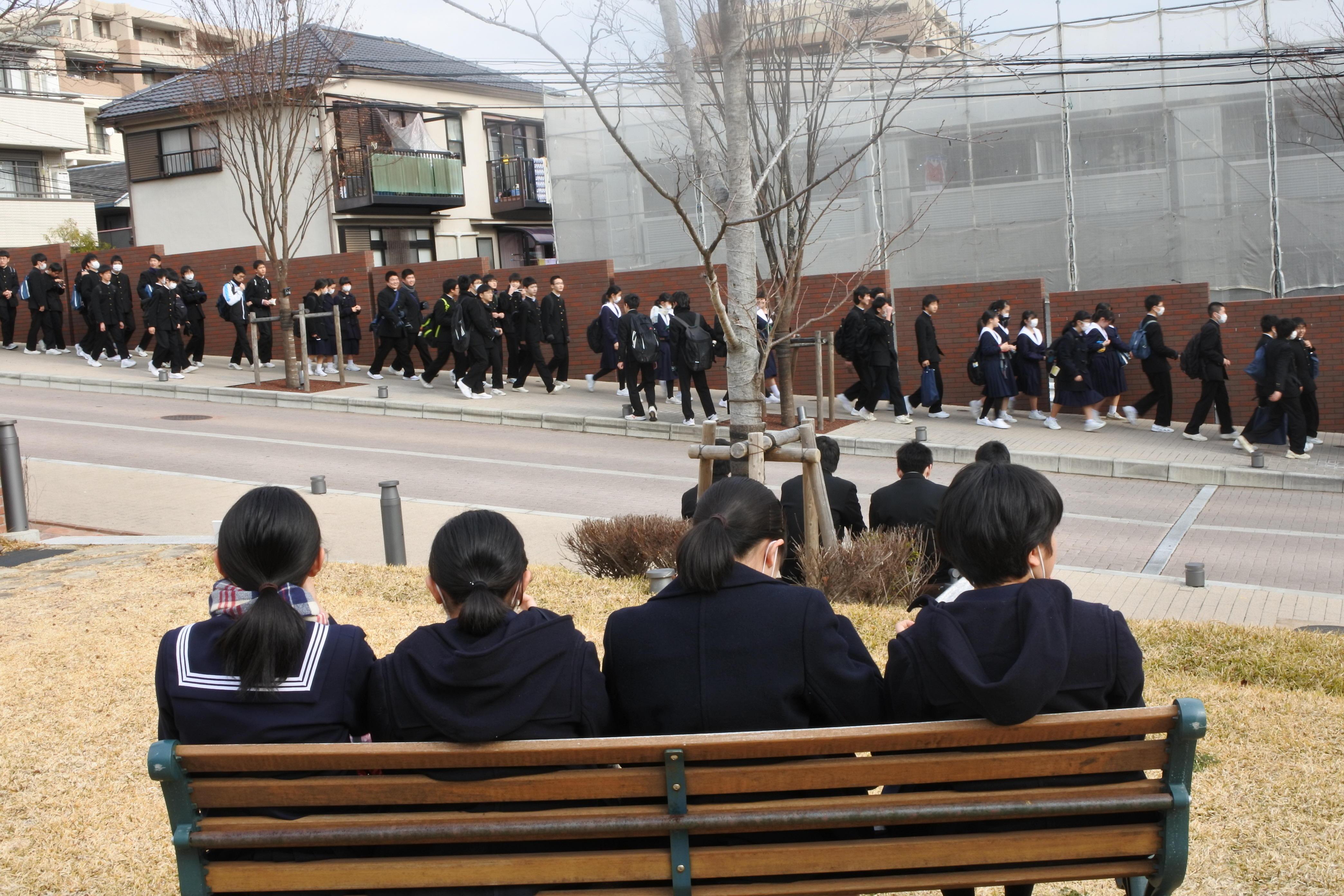 ベンチで休む中学生グループ